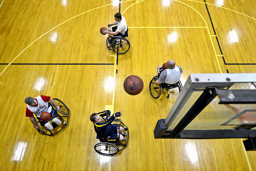 Four people playing wheelchair basketball in a sports hall
